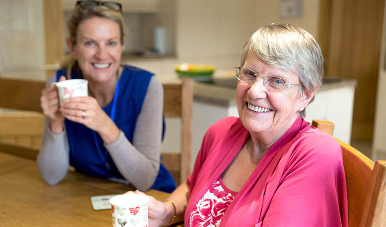 A smiling senior woman and community care worker enjoying a cup of tea in a home kitchen.